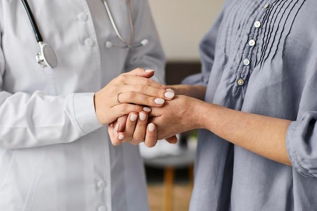 Medico femminile del centro di recupero covid che tiene le mani del paziente anziano