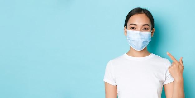 Социальное дистанцирование covid и концепция пандемии коронавируса крупным планом улыбающейся азиатской девушки в белой футболке ...