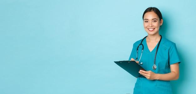 Covid социальное дистанцирование и концепция пандемии коронавируса улыбающаяся азиатская медсестра, интерн врача ...