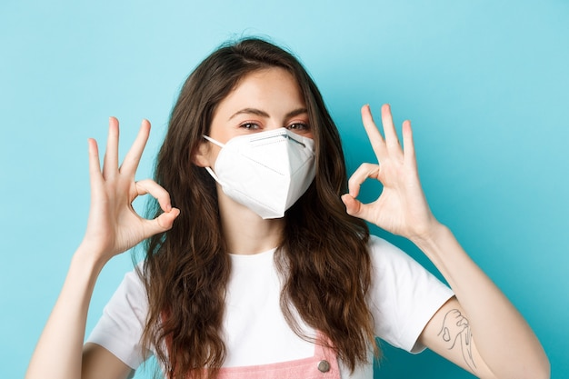 Covid social distancing and lockdown concept young positive woman in respirator showing okay signs a...