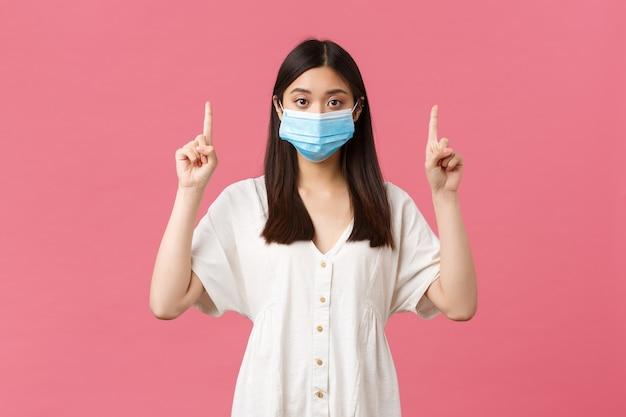 Covid社会距離拡大ウイルスとライフスタイルのコンセプト医療マスクのかなりスタイリッシュなアジアの女の子が示唆しています...