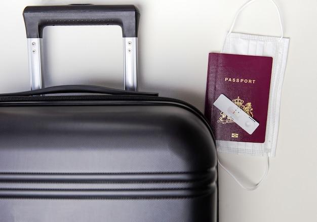 Covid旅行とテストのコンセプトpcrテストと観光パスポートと黒いスーツケースコロナウイルス