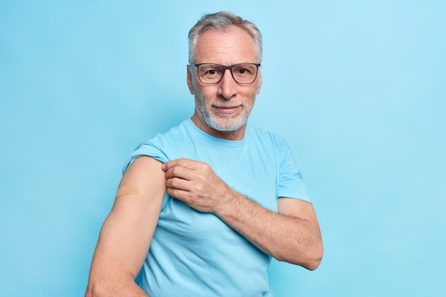 Covid vaccination concept. serious bearded grey haired man shows place of inoculation adhesive plaster on arm