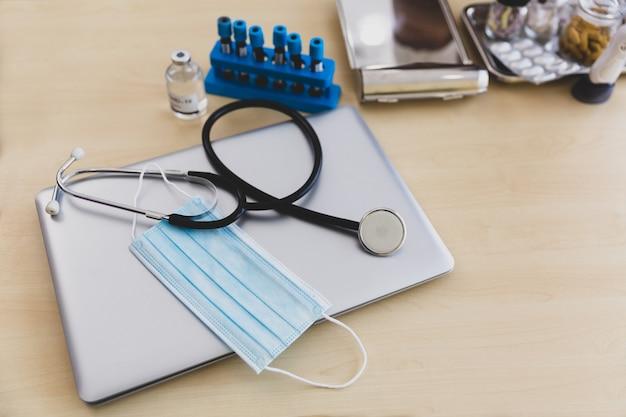 Covidワクチン、血液チューブ、医師の作業机の上のラップトップ上の医療マスク付き聴診器