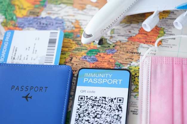 Covid vaccine passport qr code on smartphone screen and airplane with tickets digital