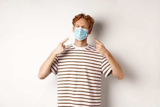 Covid、ウイルス、社会距離拡大の概念。白い背景の上に立って、フェイスマスクに指を指している赤毛の男を笑顔。
