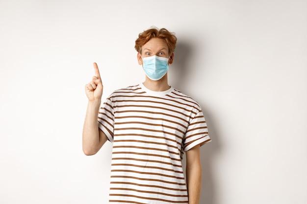 Covid、ウイルス、社会距離拡大の概念。フェイスマスクで驚いた赤毛の男が上に広告を表示し、指を上に向けて驚いた、白い背景に見える