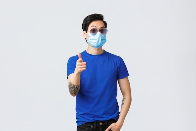 Covid019 생활 방식, 사람들의 감정, 격리 개념에 대한 여가. 매우 좋은. 선글라스와 의료용 마스크를 쓴 잘 생기고 세련된 아시아 남자, 승인에 엄지손가락을 치켜들고 좋아하거나 동의합니다.