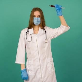 Covid19, коронавирус. портрет профессионального уверенного молодого кавказского врача в медицинской маске и белом халате, стетоскоп на шее, со шприцем с вакциной в руке, борьба с болезнью