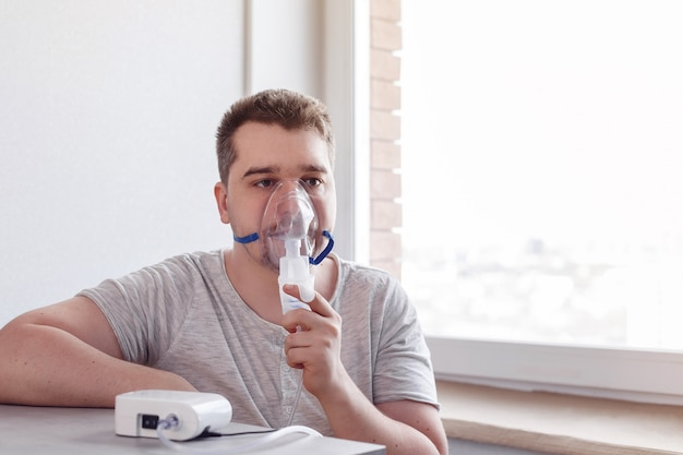 Мужчина сидит у окна с ингалятором дома. концепция лечения короновируса. лекарство в домашних условиях. covid19. pneumomania.