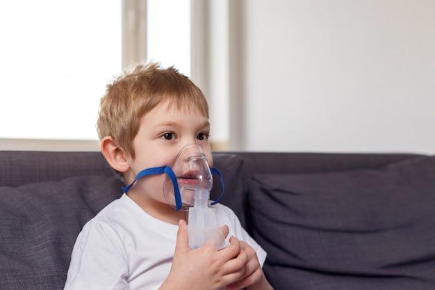 Ребенок сидит на диване с ингалятором дома. концепция лечения короновируса. утепление дома. covid19. pneumomania.