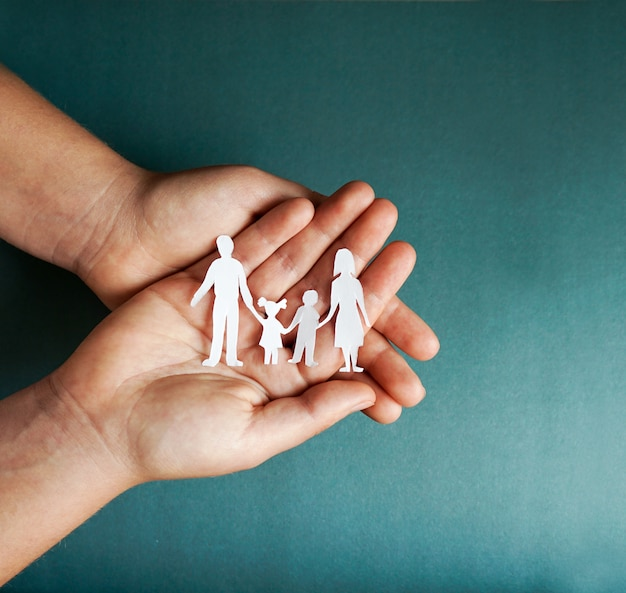 紙の家族の切り抜き、社会的距離概念、青い色の背景、家族の保護に関するcovid19を保持している手