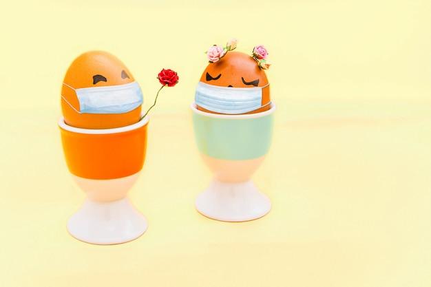 Счастливые пасхальные яйца с вирусной маской на светлом фоне, защита от вируса короны (covid19)