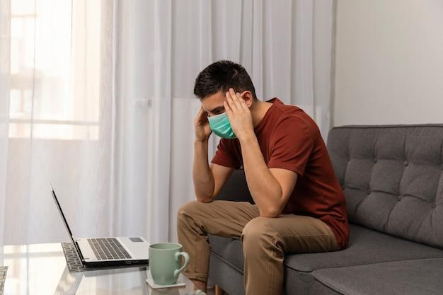 男はcovid19ウイルスに病気で、自宅で働いています。