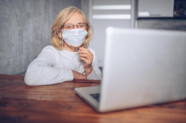 Концепция технологии, старости и людей - одинокая унылая старшая старшая женщина в маске стороны медицинской работая и звоня видео- с портативным компьютером дома во время пандемии коронавируса covid19. остаться дома