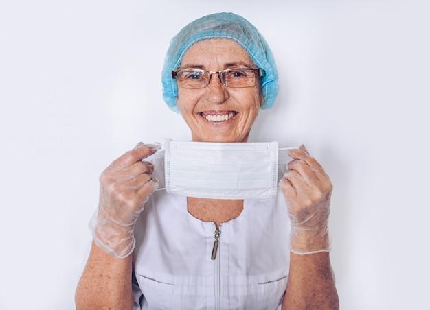 Пожилые улыбающиеся зрелая женщина-врач или медсестра в белом медицинском халате, перчатки, надевает маска для лица, носить средства индивидуальной защиты изолированы. концепция здравоохранения и медицины. covid19 пандемический кризис
