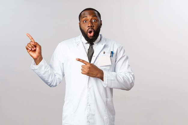 Covid19, концепция здравоохранения и клиники. удивленный афро-американский доктор в белом халате, задыхаясь, впечатлен, увидев невероятные новости, делясь информацией о ситуации с пандемией коронавируса, точка слева