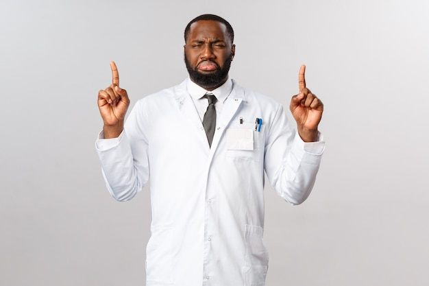 Портрет расстроенной, мрачной афроамериканской мужской медсестры или доктора, указывающей пальцами вверх и жалующейся на переутомление, загруженное расписание в больнице, усталость от работы во время пандемии covid19, вспышка короны
