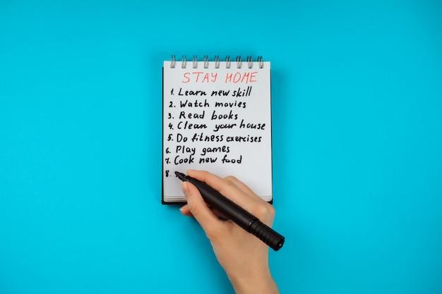 女性の手は、covid19パンデミックに対する隔離、自己隔離で家にいる間にすべきことのチェックリストを書いています。