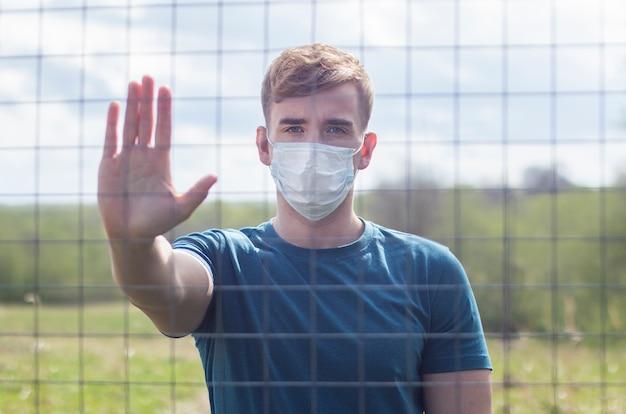 バー、格子の後ろに立っている顔に防護マスクでハンサムな男。自由の制限。自己分離、コロナウイルス流行ウイルス感染。 covid19。孤立した若い男は手のひら、一時停止の標識を表示
