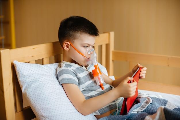 少年は、肺の吸入処置中にタブレットで遊ぶ。 covid19、コロナウイルス、パンデミック。