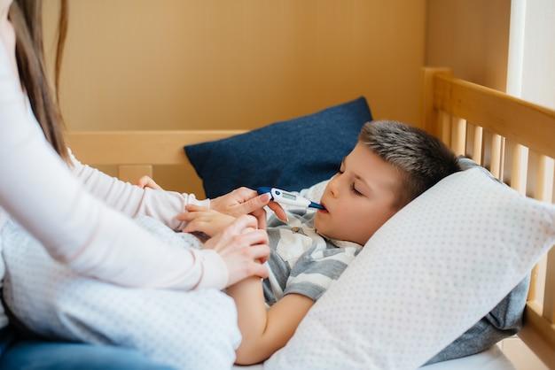発熱のある子供を母親が面倒を見る。 covid19、コロナウイルス、パンデミック。