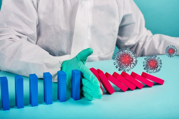 Концепция пандемии коронавируса covid19 с падающей цепью, как игра в домино. заражение и прогрессирование инфекции прекращаются рукой врача. голубая стена