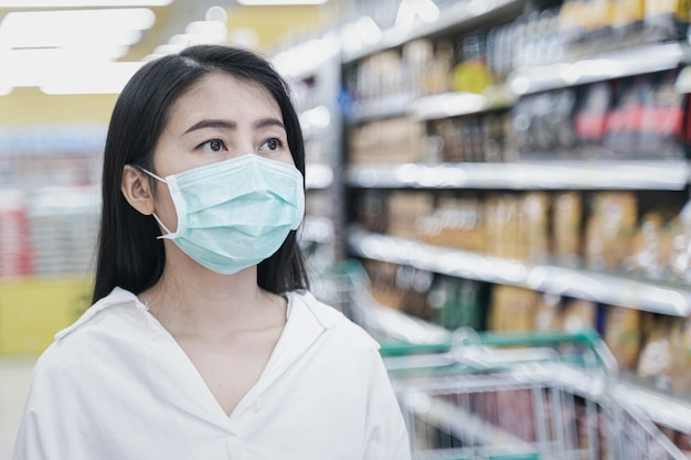 スーパーマーケットのデパートでのショッピングのフェイスマスクを着ている女性。コロナウイルスの危機またはcovid19の発生時に棚で購入する食料品を探している女の子。食料品の購入