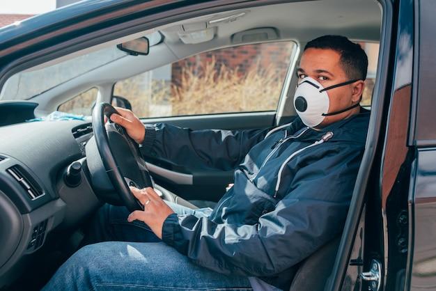 防護マスクを着用し、クライアントを待っている若いヒスパニックタクシー運転手。 covid19。コロナウイルス。
