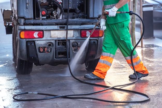 緑の作業服を着た労働者。covid19やコロナウイルスを防ぐために、加圧された漂白剤を入れた水鉄砲で通りを掃除しています。