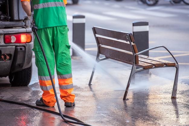 水圧銃を持つ都市労働者。 covid19、コロナウイルスの防止のための通りと通りの家具の清掃