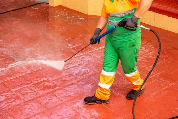 緑の作業服に身を包んだ労働者は、加圧漂白水鉄砲でcovid19またはクラウンウイルスを防止するために通りを掃除しています
