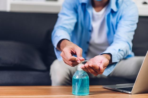 若い男が社会的距離の保護マスクを身に着けていると自宅で作業しているラップトップコンピューターを使用してコロナウイルスの検疫のアルコールゲルで手を洗うと自宅で作業しているcovid19コンセプト