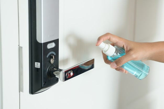ボトルから青い消毒剤をスプレーしてドアノブを消毒する女性、covid19、コロナウイルスを防止します。