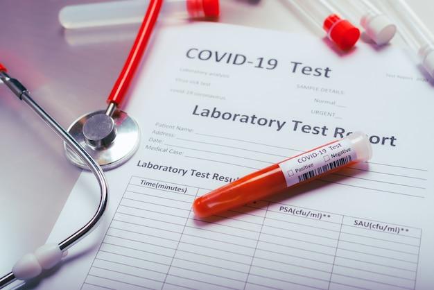 世界で感染したcovid19の報告に関する聴診器と試験管。