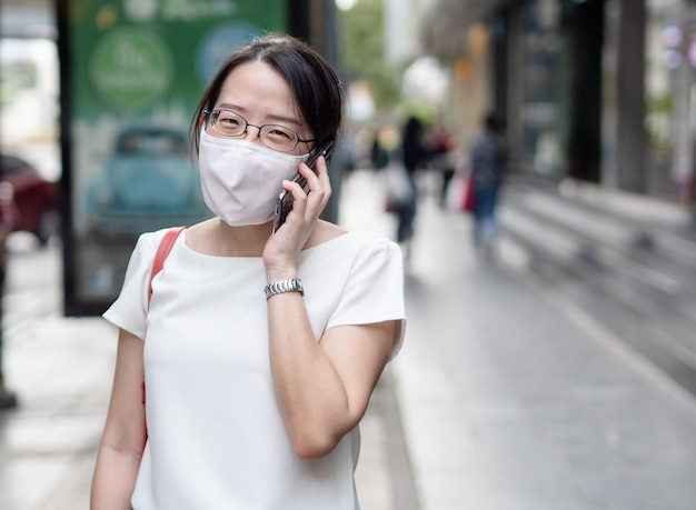 Красивые азиатские женщины носят одноразовые медицинские маски для лица, используя смартфон в общественных местах, на дорогах или в центре города, как новый нормальный тренд и самозащита от инфекции covid19.