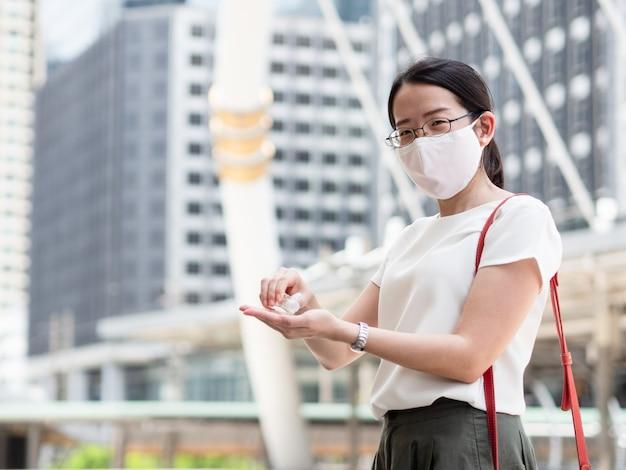 Covid19感染に対する新しい通常の傾向および自己保護として、医療用フェイスマスクを身に着けている美しいアジアの女性、公共エリアまたは市内中心部にいる間、アルコールジェルまたは消毒剤を使用して手をきれいにする