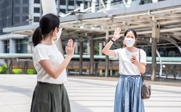 Две красивые азиатки приветствуют коллегу, надевая одноразовую медицинскую маску каждый раз за пределами дома, как новый нормальный тренд и самозащиту от инфекции covid19.