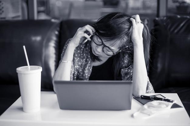 落ち込んでいるアジアの女性は家の机に座っています。 covid19またはコロナウイルスの発生の問題のため、彼女は自宅で仕事をしています。