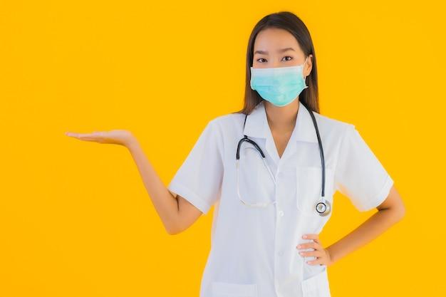 Портрет красивая молодая азиатская женщина-врач с маской для защиты covid19