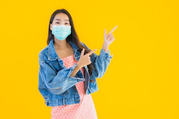 肖像画の美しい若いアジアの女性は、コロナウイルスやcovid19を保護するためのマスクを着用