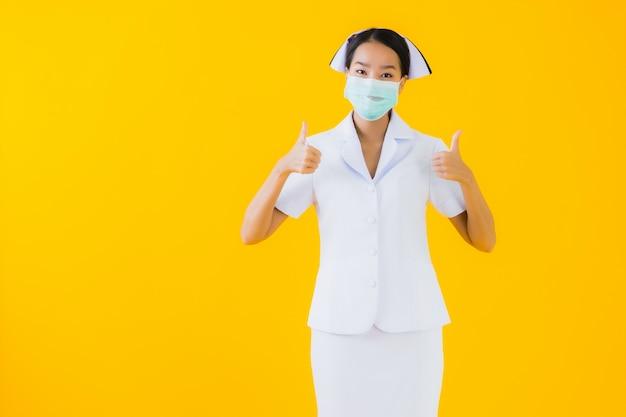 肖像画の美しい若いアジア女性タイの看護師はcovid19またはコロナウイルスを保護するためのマスクを着用します