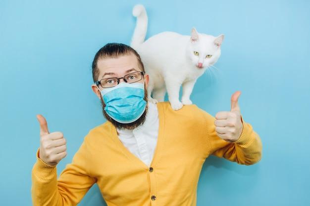 彼の肩に白猫と医療マスクの陽気な男。パンデミックcovid2019。ペット。