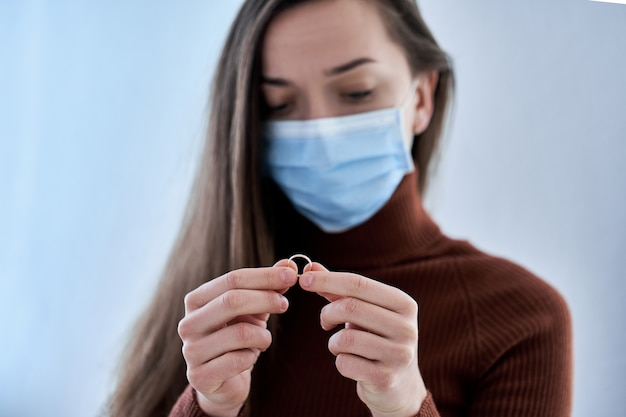 防護マスクの女性はリングを保持しています。コロナウイルスcovidの流行により、隔離および隔離中に同居し、夫と一緒に家に滞在した後の関係を解消する。離婚のコンセプト