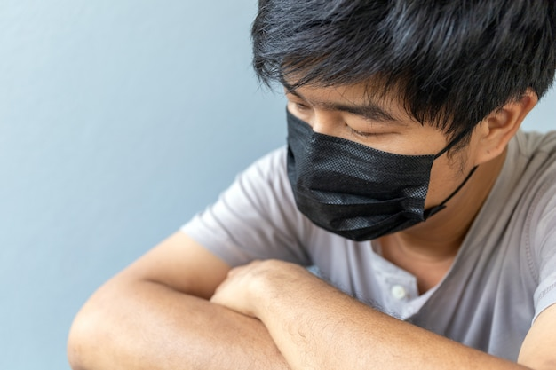 ソフトフォーカスでコロナウイルス(covit-19)を保護するマスクを身に着けているクローズアップ男性