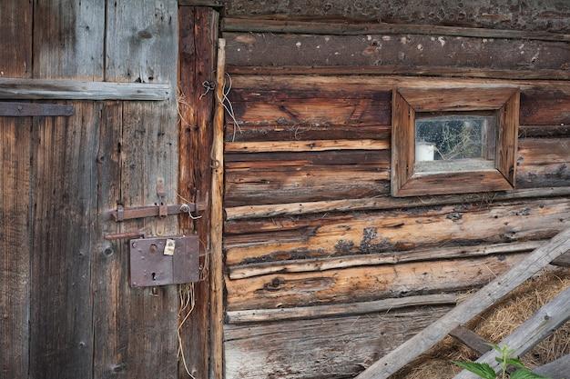 小さな窓とドアが付いている牛の納屋の壁