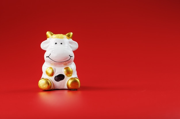Cow figurine on a red background, new year's concept.