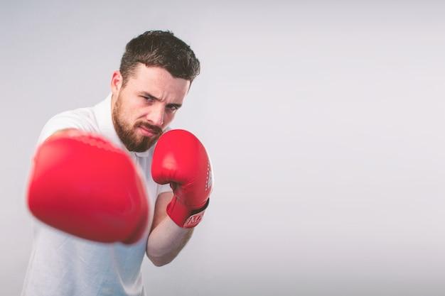 赤いボクシンググローブで臆病な面白い若い男。オタクは眼鏡をかけています。
