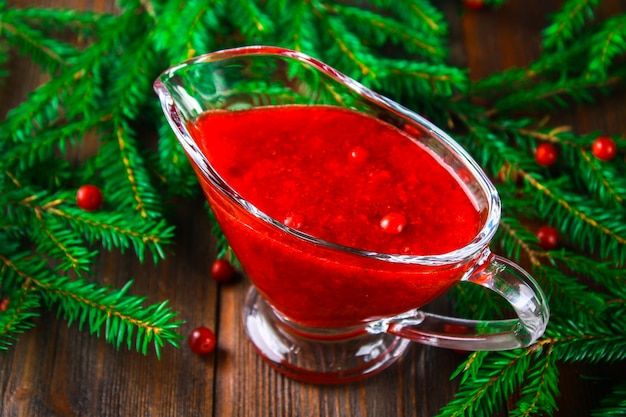Cowberry cranberry sauce in a glass clear saucer on a wooden table with spruce branches.