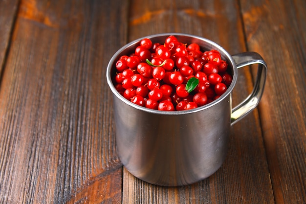 Cowberry, foxberry, cranberry, lingonberry in an aluminum mug on a brown wooden table.